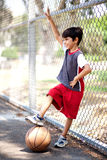 Smiling young boy with his basketball. Resting against fence Stock Photos