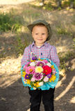 Smiling young boy holding flowers Royalty Free Stock Photos