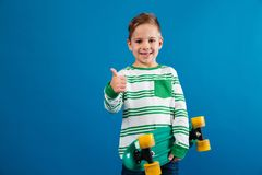 Smiling young boy holding skateboard and showing thumb up. At camera over blue background Royalty Free Stock Photo