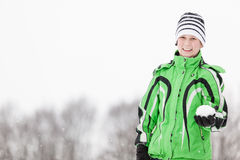 Smiling young boy holding a snowball. In his gloved hand as he prepares to have a mock snowball fight with his friends, upper body in fashionable winter clothes Royalty Free Stock Photography