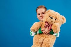 Smiling young boy holding teddy bear and looking at camera. Smiling young boy holding teddy bear and looking at the camera over blue background Royalty Free Stock Images