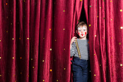 Smiling young boy impatient for his performance. In the pantomime to begin peering out from between the burgundy curtains in his costume and makeup stock photography