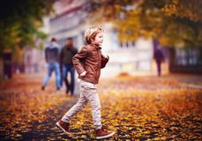 Smiling young boy, kid having fun in autumn city park among fallen leaves stock photos