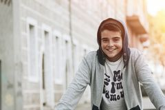 Smiling young boy leaning on a wall. Outdoor portrait of a happy smiling young boy wearing a light gray  jacket with a dark gray hood, leaning forward against a Stock Photos