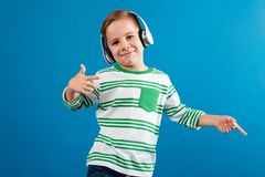 Smiling young boy listening music and dancing. Over blue background Royalty Free Stock Photos