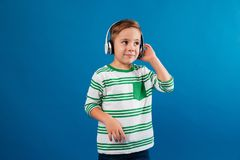 Smiling young boy listening music by headphone and looking aside. Over blue background Royalty Free Stock Photography