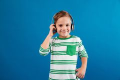 Smiling young boy listening music by headphone Royalty Free Stock Photos