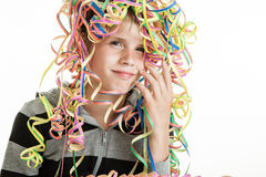 Smiling young boy with party streamers on his head. Smiling young boy with a colorful tangle party streamers on his head, conceptual of a birthday, carnival Stock Images