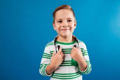 Smiling young boy posing with headphone and looking away. Over blue background Stock Images