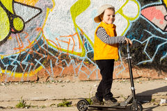 Smiling young boy posing on his scooter Stock Images