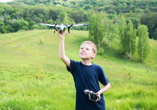 Smiling young boy preparing to launch RC plane. Beautiful nature background. Stock Photography