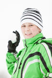 Smiling young boy preparing to throw a snowball. Smiling young boy in winter gloves , green jacket and knitted beanie cap preparing to throw a snowball at the Royalty Free Stock Images
