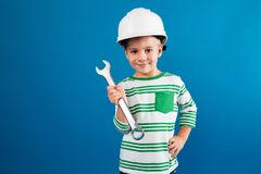 Smiling young boy in protective helmet posing with wrench. Like engineer and looking at the camera over blue background Royalty Free Stock Photo