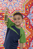 Smiling Young Boy with Ramadan Lantern. Smiling Young Boy with Vintage Lantern over Festive Ramadan Fabric Royalty Free Stock Photo