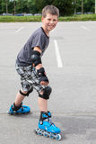 Smiling young boy ready to start riding on roller skates in summer urban park Stock Photography