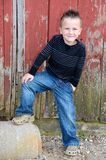 Smiling young boy by red barn. Cute smiling young boy wearing denim blue jeans with foot on drainage pipe by red weathered barn Stock Photo