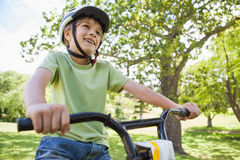 Smiling young boy riding bicycle at park Stock Photos