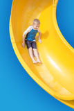 Smiling Young boy riding down a yellow water slide Stock Photography