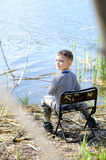 Smiling Young Boy Sitting on a Chair While Fishing Stock Image