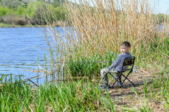 Smiling Young Boy Sitting on a Chair While Fishing Stock Photo