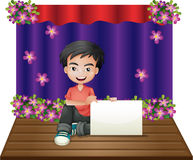 A smiling young boy sitting in the middle of the stage holding a vector illustration