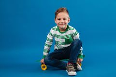 Smiling young boy sitting on skateboard and looking at camera. Smiling young boy sitting on skateboard and looking at the camera over blue background Royalty Free Stock Image