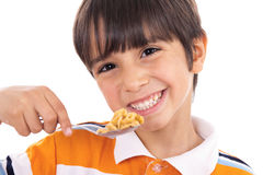 Smiling young boy with spoon of flakes, closeup. On isolated white background Royalty Free Stock Image