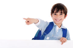 Smiling young boy standing behind the blank board. And pointing us on isolated white background Stock Photos