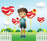 A smiling young boy standing in the garden with giant heart loll Royalty Free Stock Images
