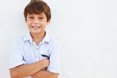 Smiling Young Boy Standing Outdoors Against White Wall Royalty Free Stock Image