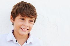 Smiling Young Boy Standing Outdoors Against White Wall Royalty Free Stock Images