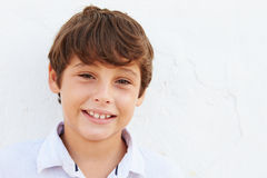 Smiling Young Boy Standing Outdoors Against White Wall Royalty Free Stock Photography