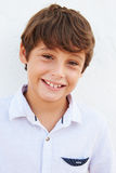 Smiling Young Boy Standing Outdoors Against White Wall Stock Photos