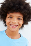 Smiling Young Boy Standing Outdoors Against White Wall Stock Photography