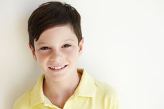 Smiling Young Boy Standing Outdoors Against White Wall Stock Image