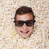 Smiling young boy in stereo glasses looking out of popcorn. Smiling young boy in stereo glasses watching a movie from popcorn Stock Photos