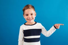 Smiling young boy in sweater pointing away. And looking at the camera over blue background Royalty Free Stock Photo