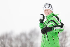 Smiling young boy taking aim with a snowball Royalty Free Stock Photos