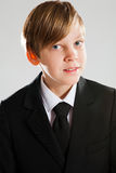 Smiling young boy wearing black suit. Studio portrait of a happy smiling young boy wearing black suit Royalty Free Stock Images