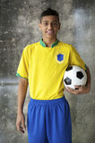 Smiling Young Brazilian Soccer Player in Uniform Holding Football Stock Photo