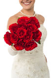 Smiling young bride holding out a rose bouquet Royalty Free Stock Photos