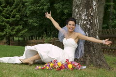 Smiling young bride sitting under tree Stock Photo