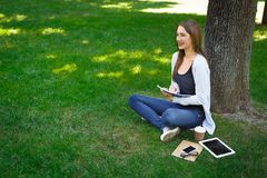 Young brunette asian girl relaxing on a grass and making notes in the park during the day. Smiling young brunette asian girl relaxing on a grass and making notes Royalty Free Stock Images