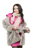 Smiling young brunette in a fur coat Stock Photos