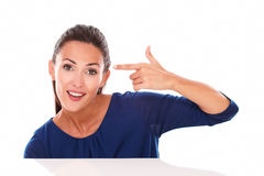 Smiling young brunette gesturing a headshot Royalty Free Stock Photo