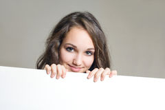 Smiling young brunette girl with blank white sign. Stock Photography
