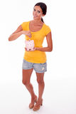 Smiling young brunette with piggy bank. Smiling brunette holding a pink piggy bank in front of her while looking at camera and wearing a yellow t-shirt and short Stock Image