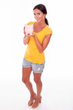 Smiling young brunette with piggy bank. Smiling brunette holding a pink piggy bank in front of her while looking at camera and wearing a yellow t-shirt and short Royalty Free Stock Image