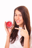 Smiling young brunette woman with alarm clock Stock Photography