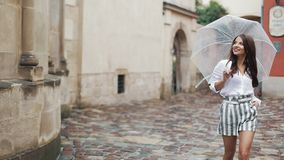 Smiling young brunette woman in dress walks with umbrella along the street of an old town. Walking under the rain